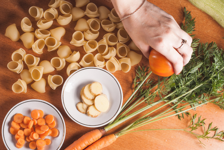 the hands of the chef and organic food on a wooden table, the pasta and set of vegetables, vegetarian cooking
