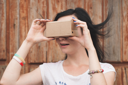 Young girl having fun playing with your cardboard VR headset attached to her smartphone. playful girl in a white t-shirt Stock Photo