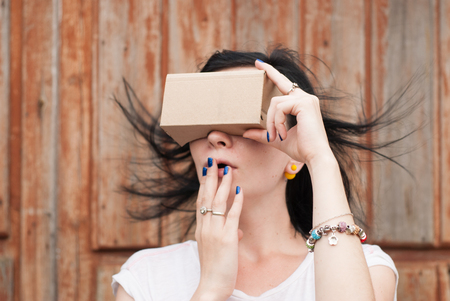 bp: Young girl having fun playing with your cardboard VR headset attached to her smartphone. playful girl in a white t-shirt Stock Photo