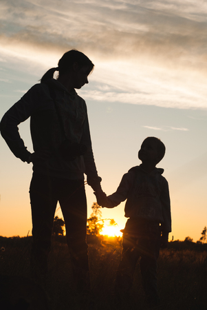 adult hand: Silhouette of mother and baby at sunset, the boy holds his mothers hand Stock Photo