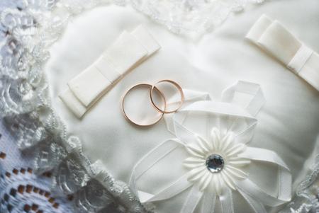 Golden wedding rings on white pillow a