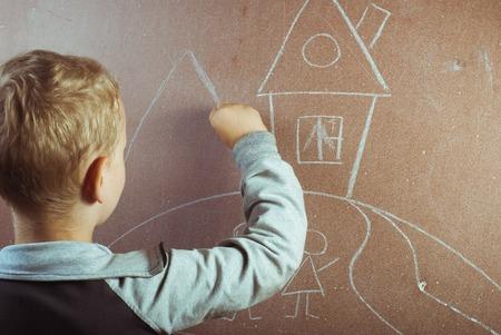 Un ragazzino disegna con il gesso su una lavagna, una lezione di disegno a scuola, torna a scuola