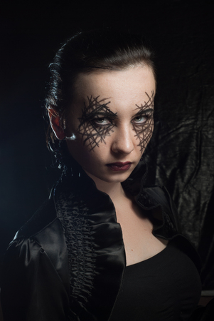 Young beautiful girl with make-up for Halloween, body art on a womans face, mystical makeup