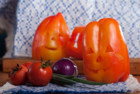 Sweet peppers on wooden table, pumpkin face for Halloween, gala dinner