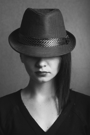 actress: Style Noir: actress in the hat, hidden look under the hat, black and white portrait of brunette
