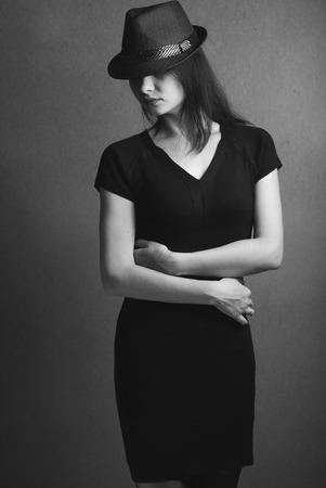 noir: Style Noir: actress in the hat, hidden look under the hat, black and white portrait of brunette