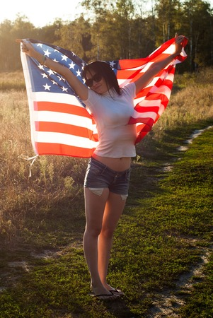 The girl with the American flag outdoors, stars and stripes flag flutters in the wind, happy patriots day Stock Photo