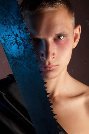 impassive: A young man in the image of a maniac with a rusty saw in his hand, a portrait in the style of horror for Halloween