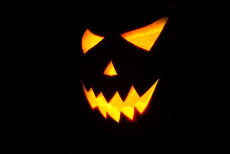 Halloween Jack-o-lantern on a black background, pumpkin with glowing in the dark eyes, the horror on Halloween Stock Photo