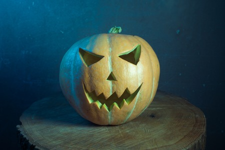 Jack-o  - lantern in cool tones on a wooden background, three-dimensional and bright light