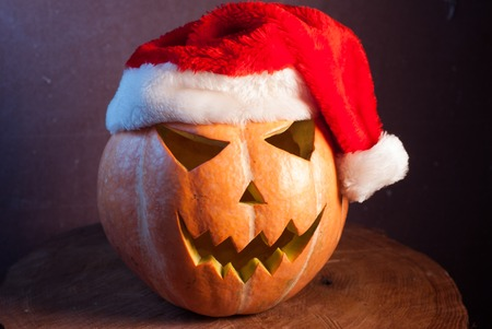 Jack-o  - lantern in a red Santa hat, happy holidays Stock Photo