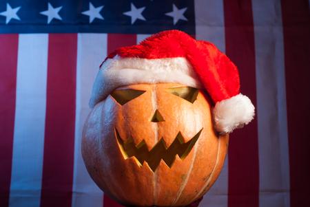 Jack-o - lantern in a red Santa hat on American flag background, happy holidays, Jack-o  - lantern-patriot