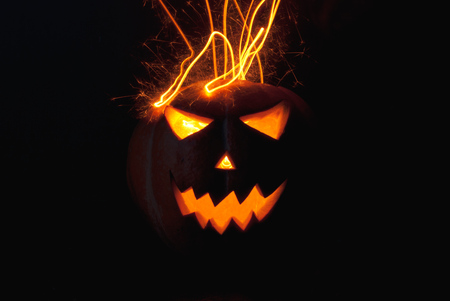 spewing: Jack-o  - lantern scary shining eyes in the darkness. Pumpkin spewing sparks. The Eve Of Halloween Stock Photo