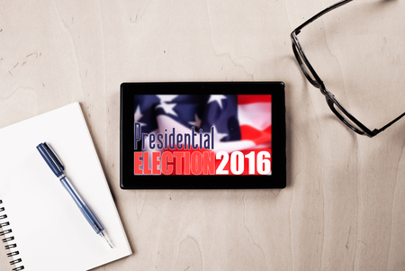 american table: tablet with American flag on wooden table, glasses, pen and Notepad, promotion of popular elections in the United States