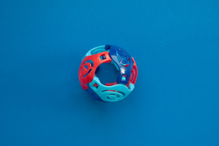Colorful Toy ball with slits on a blue background, hollow, fun for kids Stock Photo