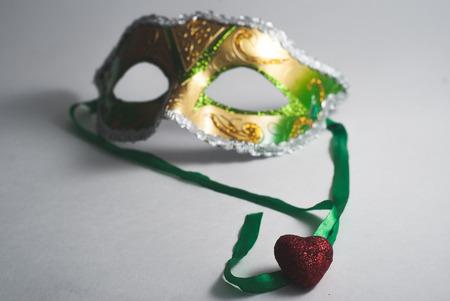 yellow green Venetian in disfocused, decorative heart, the concept of carnival, Gras Mardi