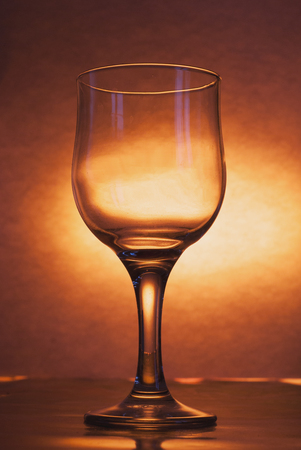 The glass is empty on a bright yellow background, the concept of alcoholic drinks, minimalism