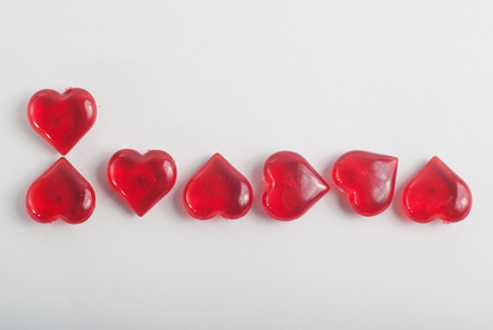 Decorative red heart glass on a white background, the inscription of hearts, March 8, heart-letters