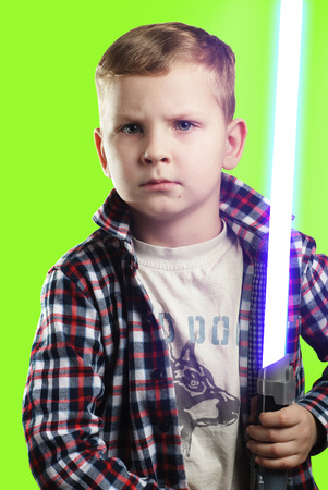 Little boy posing with a laser sword on a green background , blue bright light, a young boy with a serious face, an aspiring actor, Stock Photo