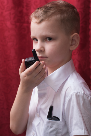 Boy with a walkie-talkie, a child in a white shirt, red background,