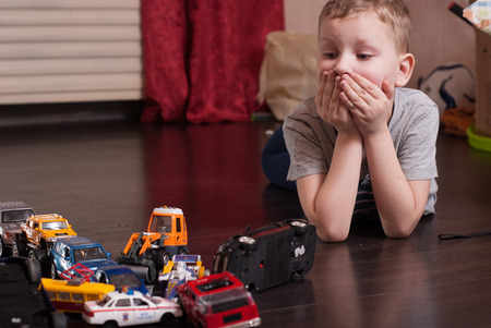 Surprised child, a traffic jam of toy cars, little boy playing, the emergency situation on the road, the conceptual