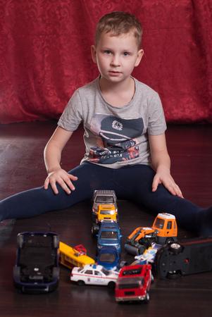 Muchos coches de juguete, niño pequeño que juega en el suelo, la situación de emergencia en la carretera, lo conceptual, piso de madera oscura Foto de archivo - 80243864