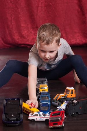 Muitos carros de brinquedo, garoto jogando no chão, a situação de emergência na estrada, o assoalho de folhosa conceitual, escuro Foto de archivo - 80243863