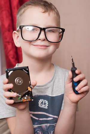 Little boy in big glasses, smart, student, examines a hard disk, a boy with a screwdriver, unscrews a screw, a small specialist, student