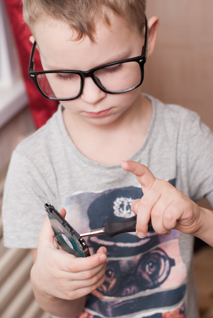 hard disk: Little boy in big glasses, smart, student, examines a hard disk, a boy with a screwdriver, unscrews a screw, a small specialist, student