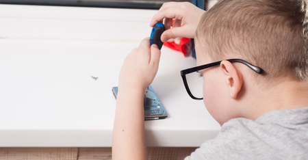Little boy in glasses with a screwdriver, disassembly the hard disk, the boy busy, a young engineer