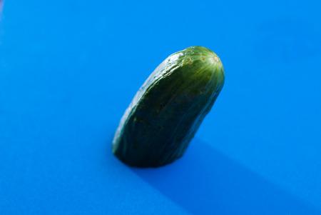 Half green a cucumber on blue background,