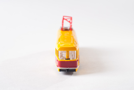 Toy tram in yellow on white background, public transport,