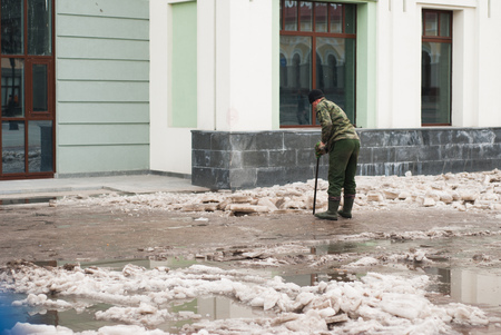 A man clears the sidewalk of ice, the worker of municipal services on the street, late spring, on the background of the Windows of the building,