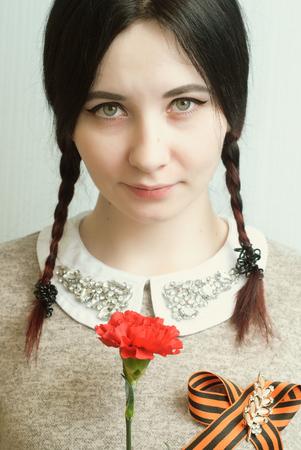 勝利の日、おさげ髪、休日の記号、聖ジョージのリボンと赤のカーネーション、愛国者とかわいい女の子 写真素材