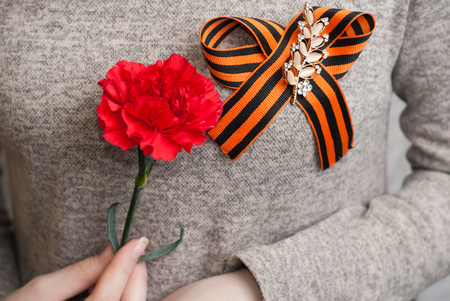 A girl holds a red carnation, St. George ribbon on clothing, Patriotic man, may 9, victory day Stock Photo
