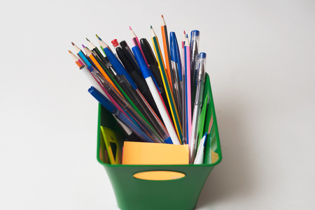 Markers, pens, pencils in a green basket