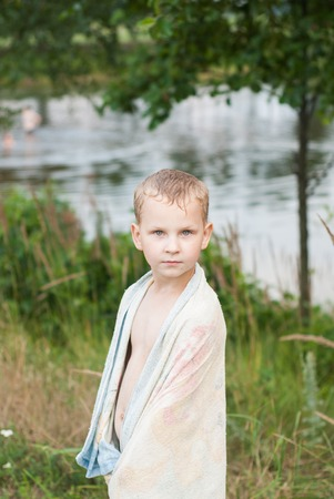 Little boy cover with a tea towel on the shores of forest lake