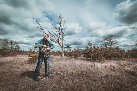 Cowboy folds the rope, the man in the hat and denim clothes, dramatic landscape: a dry tree, the clouds in the sky.