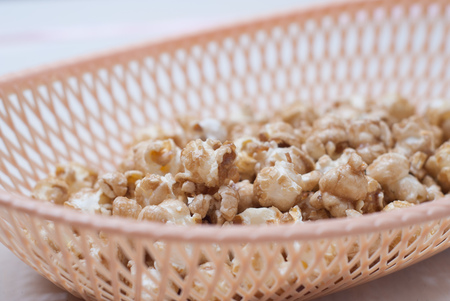 sweet popcorn in a wicker basket on a light background, a light snack, junk food