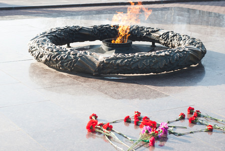 Eternal flame in honor of the fallen Soviet soldiers during the Second world war, red carnations Stock Photo