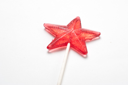 Lollipop in a star shape on white background, red candy on a stick, the symbol of the Patriotic war