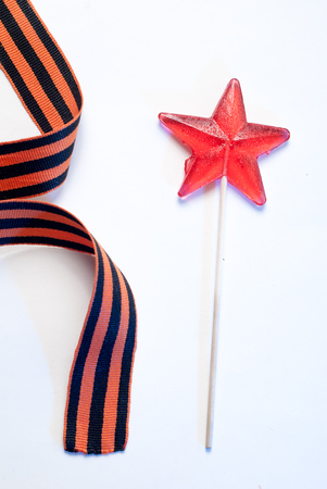 Lollipop in a star shape on white background, red candy on a stick, St. George ribbon, the symbol of the second world war