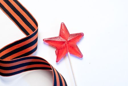 Candy in the shape of a star, a red candy on a stick,