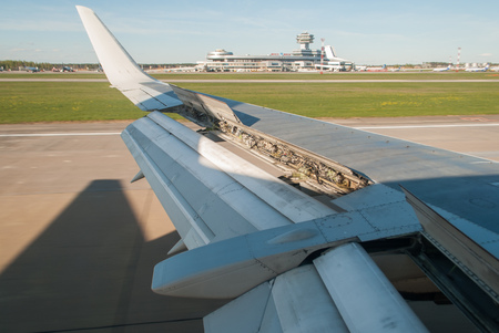 The wing of the aircraft during landing on the background of the airport, the position of the flap, Stock Photo