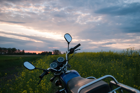 Motorcycle at sunset, rapeseed field, picturesque scenery, adventure time on a motorcycle Stock Photo