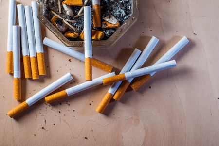 A dirty ashtray with cigarette butts scattered filter cigarettes on a wooden table,