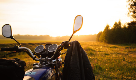 chrome man: classic motorcycle at sunset, on a grass background, the journey on a motorcycle