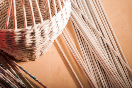 Wicker basket on a wooden table, paper tubes from the paper, crafts with their hands Reklamní fotografie