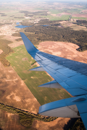 trip over: Fields and forests under the wing of the aircraft, the view from the window of an airplane, travel in the plane