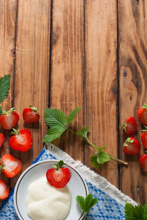 wooden floors: strawberries and whipped cream on old wooden table background, composition with freshly picked strawberries and leaves, copy space, healthy food, rustic style